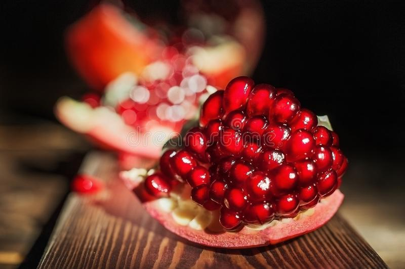 Foto van een macro van het granaatappelfruit Het close-up van granaatappelzaden op een donkere achtergrond stock fotografie