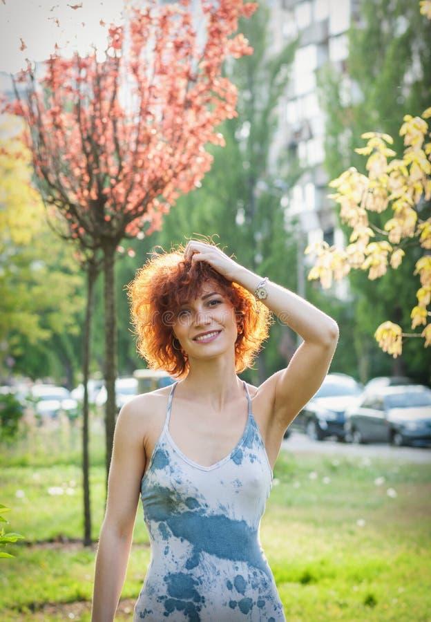 Foto van een mooi roodharigevrouw of een meisje in het park zonneschijn stock afbeeldingen