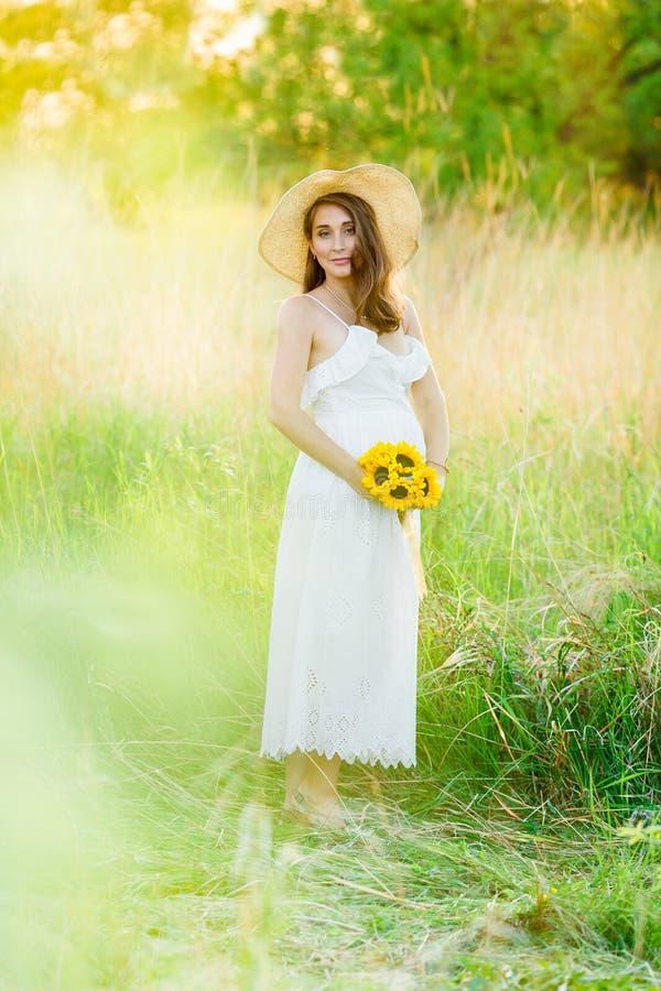 Foto van een mooi zwanger meisje in een witte kleding en strohoed die zich bij zonsondergang op een geel gebied bevinden Gelukkig stock foto