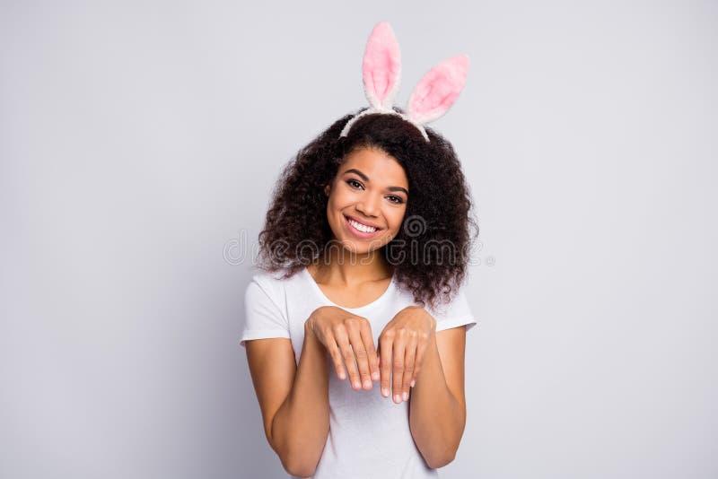 Foto van een mooie, grappige, donkere huidsvrouw, aangename, tanden glimlach, houd twee handen vast, zoals bunny paws een fluffy  royalty-vrije stock foto