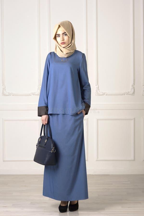 Foto van een mooie vrouw in de moderne Moslimkleren met zak en sjaal op de klassieke lichte achtergrond royalty-vrije stock afbeelding