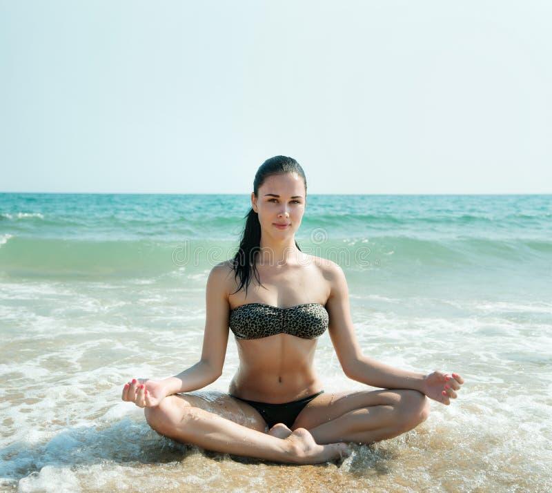 Foto van een mooie vrouw die en op een bea ontspannen mediteren stock foto's