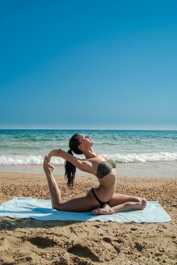 Foto van een mooie vrouw die yogaoefening op een strand o doen royalty-vrije stock afbeelding