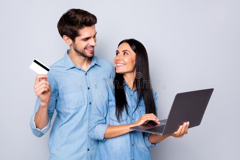 Foto van een stijlvol, trendy paar mensen uit een zakelijk gezin met hem die een creditcard bij zich heeft en haar laptop die zic stock fotografie