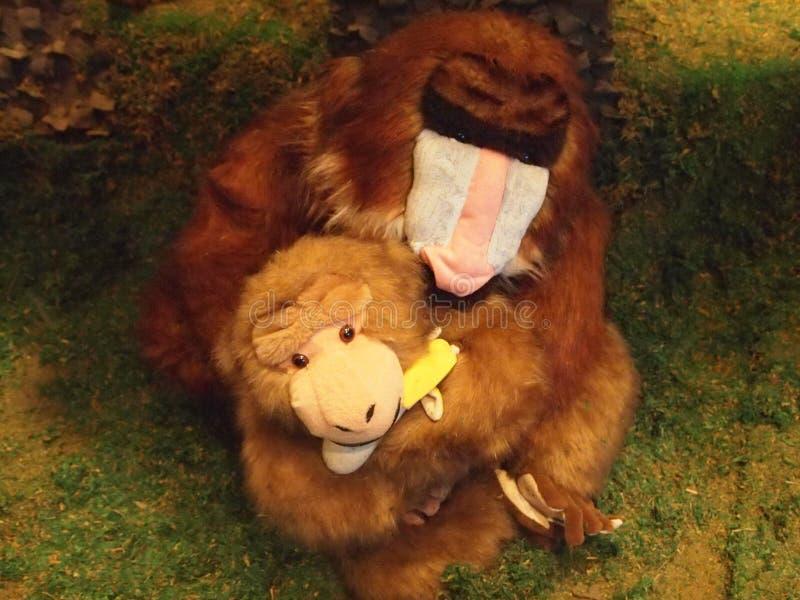 Foto van een stuk speelgoed aapmoeder die een stuk speelgoed aap houden royalty-vrije stock foto