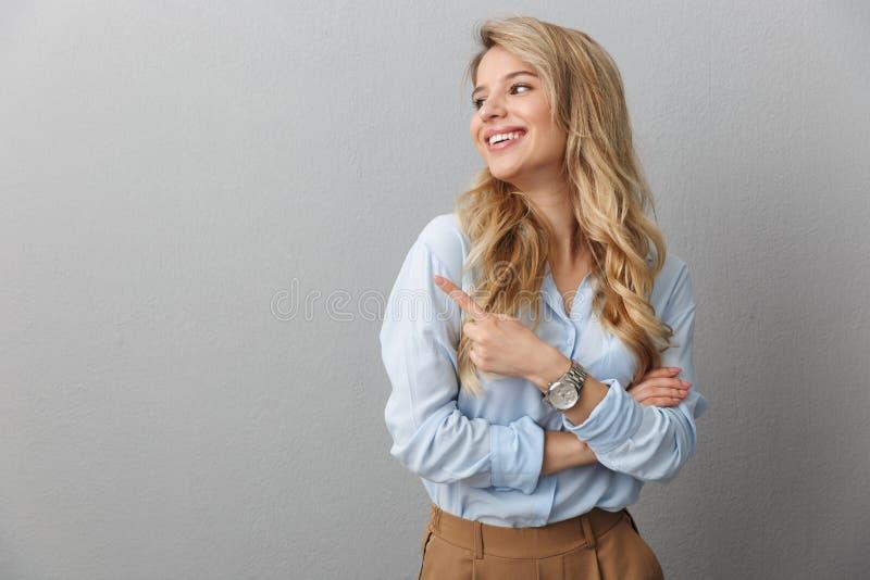 Foto van een tevreden blonde zakenvrouw met een lang krullend haar die glimlacht en met de vinger opzij wijst bij de copyspace stock afbeeldingen