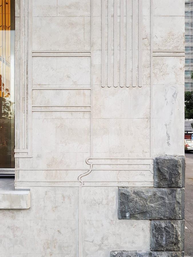 Foto van een witte muur met antiquiteiten bas-hulp en een van beneden naar boven geschotene kolom royalty-vrije stock fotografie