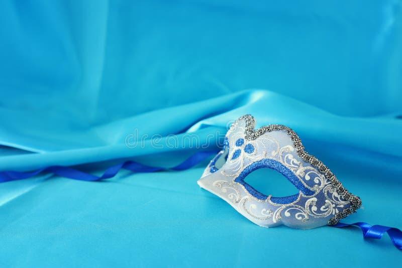 Foto van elegant en gevoelig zilveren en blauw Venetiaans masker over turkooise zijdeachtergrond royalty-vrije stock foto
