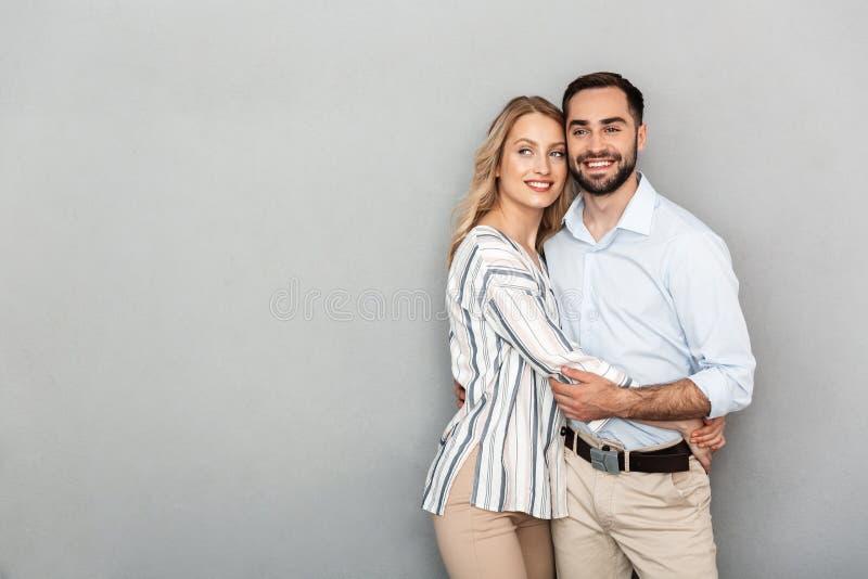 Foto van Europees paar in toevallige kleding die en elkaar glimlachen koesteren stock afbeeldingen