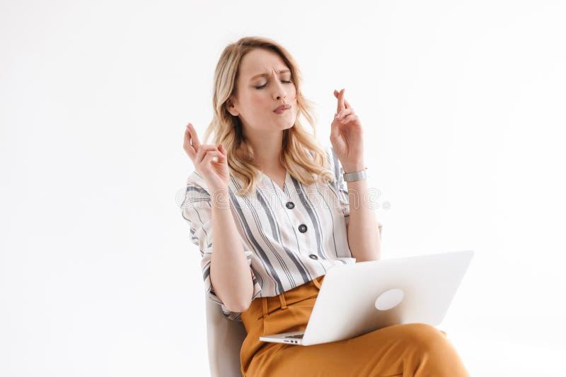 Foto van Europese geconcentreerde vrouw die vrijetijdskleding dragen gebruikend laptop en kruisend haar vingers terwijl het zitte royalty-vrije stock fotografie