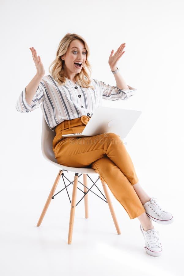 Foto van Europese opgewekte vrouw die vrijetijdskleding dragen die laptop bekijken terwijl het zitten als voorzitter royalty-vrije stock foto's