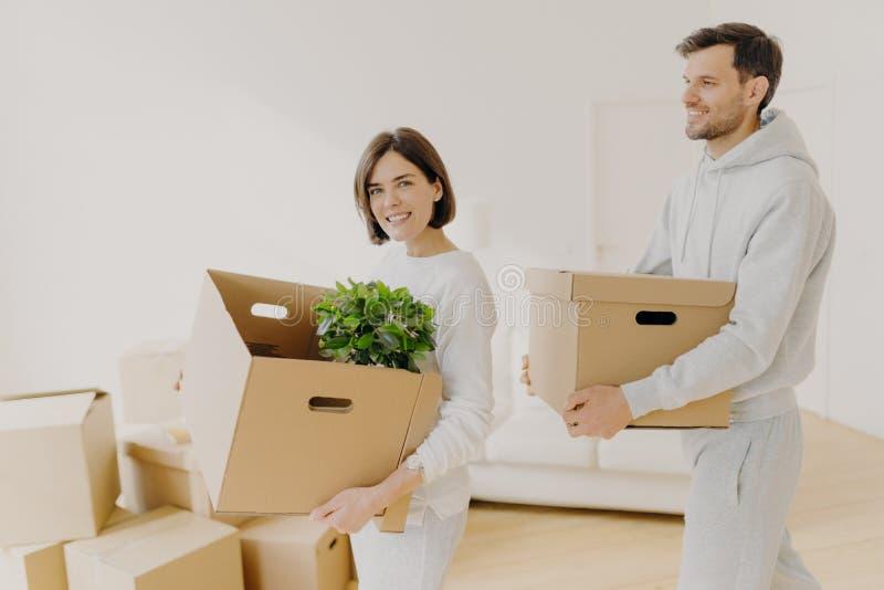 Foto van familieparen zijn grote dozen met huishoudartikelen en persoonlijke bezittingen, verhuizen naar een nieuw huis, geven ee royalty-vrije stock foto's