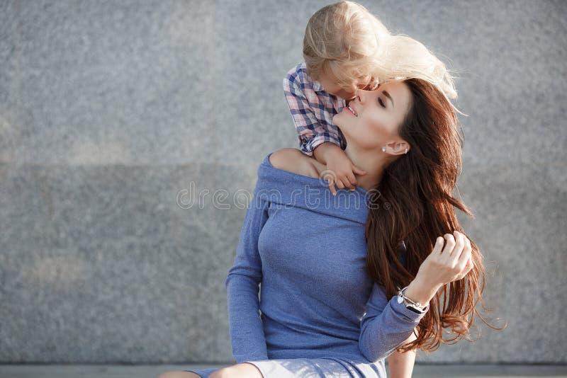 Foto van gelukkige dochter en moeder die in openlucht op de achtergrond die van de stad lopen, het weekend samen doorbrengen royalty-vrije stock fotografie