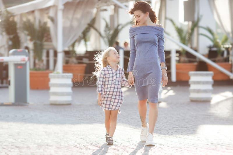 Foto van gelukkige dochter en moeder die in openlucht op de achtergrond die van de stad lopen, het weekend samen doorbrengen royalty-vrije stock foto's