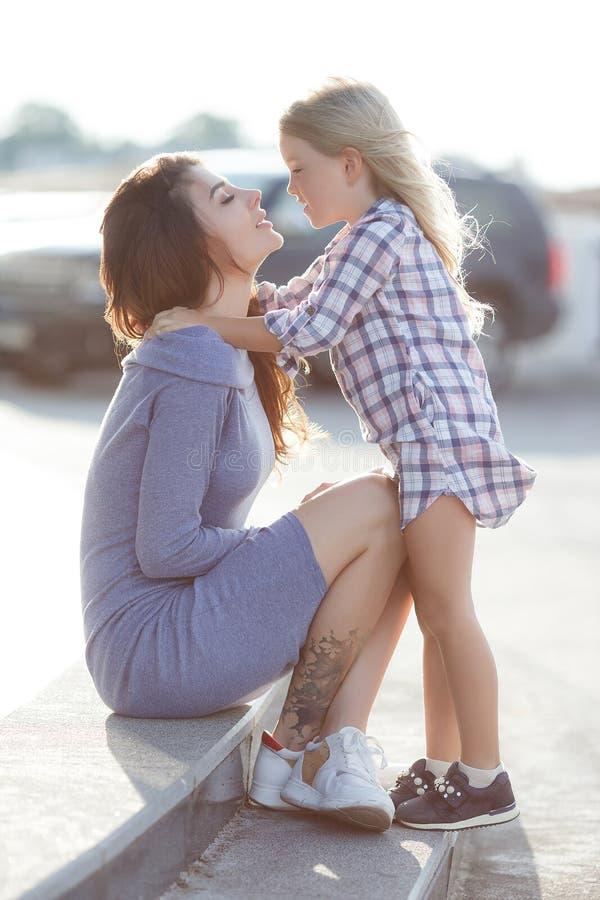 Foto van gelukkige dochter en moeder die in openlucht op de achtergrond die van de stad lopen, het weekend samen doorbrengen royalty-vrije stock afbeeldingen