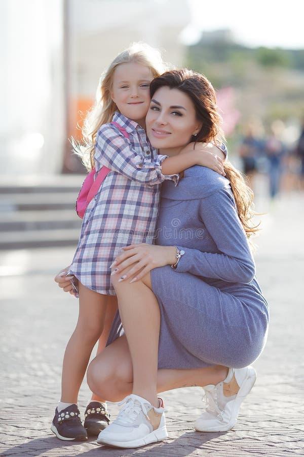 Foto van gelukkige dochter en moeder die in openlucht op de achtergrond die van de stad lopen, het weekend samen doorbrengen stock foto
