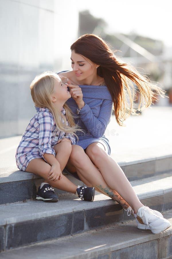 Foto van gelukkige dochter en moeder die in openlucht op de achtergrond die van de stad lopen, het weekend samen doorbrengen stock afbeeldingen