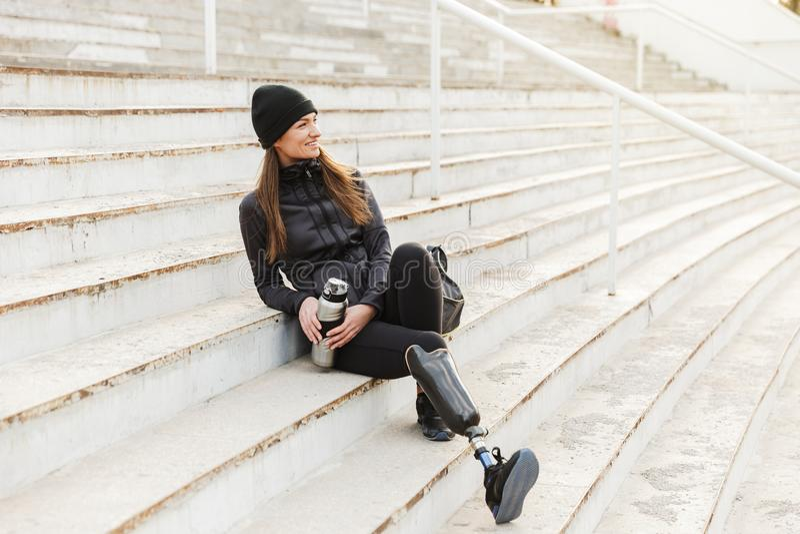 Foto van gelukkige gehandicapte vrouw in zwarte sportkleding met prosth stock fotografie