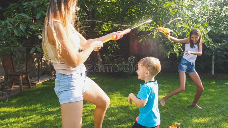 Foto van gelukkige kinderen die de strijd van het waterkanon hebben bij de tuin van de huisbinnenplaats Familie die en pret spele stock afbeeldingen
