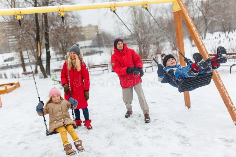 Foto van gelukkige meisje en jongen die in de winter in park met ouders slingeren stock fotografie