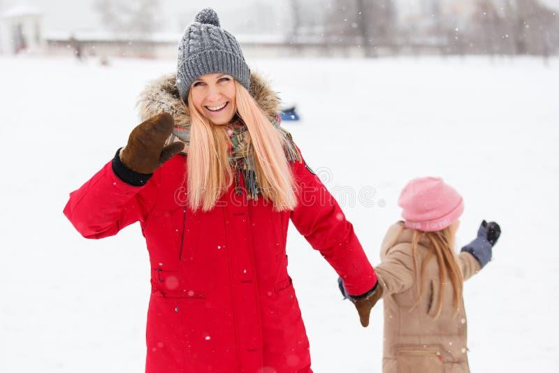 Foto van gelukkige moeder en dochter op gang in de winterpark royalty-vrije stock foto's
