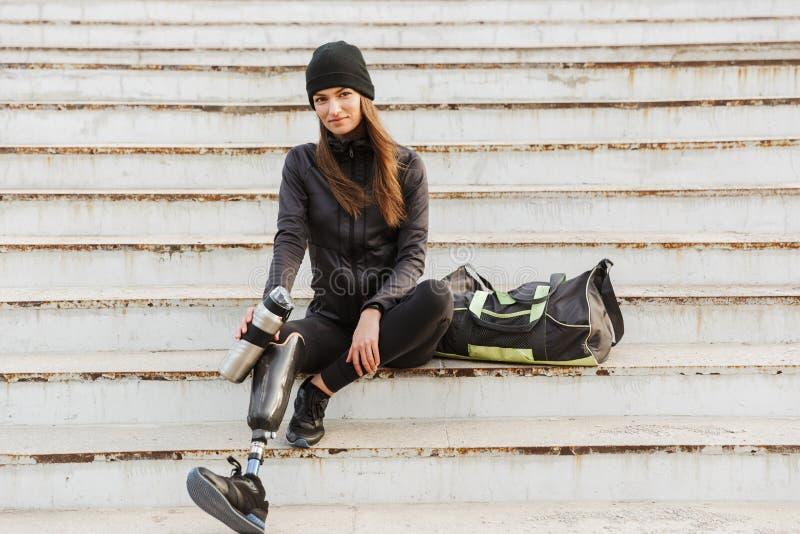 Foto van glimlachende gehandicapte vrouw in sportkleding met prothetisch stock afbeeldingen