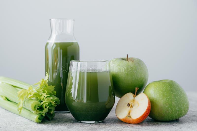 Foto van groene smoothie met cerely en appel in twee glascontainers op witte achtergrond Gezond organisch sap Het op dieet zijn c stock afbeeldingen
