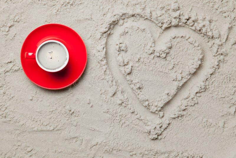 Foto van hart gevormde tekening en kop van koffie op het zand stock afbeelding