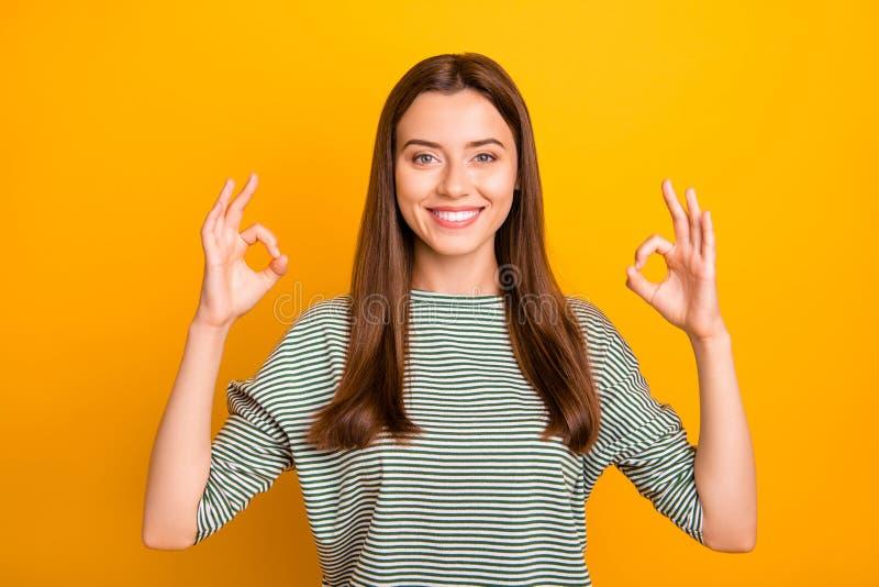 Foto van het charmeren van schitterende vrouw die ons dubbel o.k. teken geven terwijl geïsoleerd met gele achtergrond stock foto's