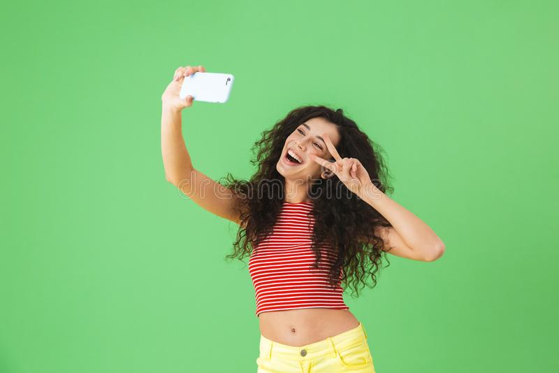 Foto van het charmeren van vrouw die en celtelefoon voor selfie over groene achtergrond glimlachen met behulp van stock foto's