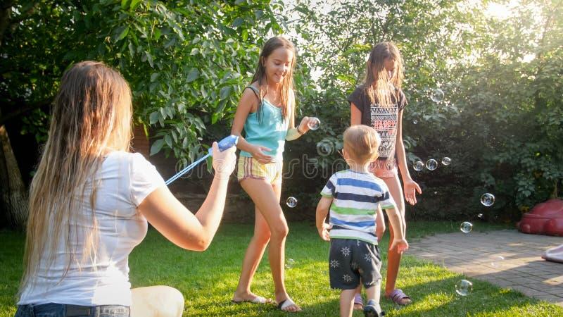 Foto van het gelukkige familie spelen met zeepbels bij de tuin van de huisbinnenplaats Familie die en pret spelen hebben in openl royalty-vrije stock fotografie