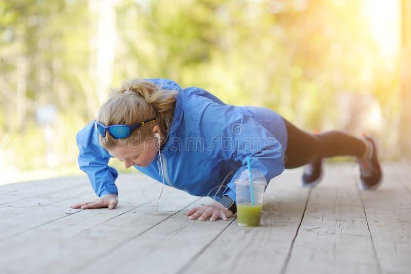 Foto van het jonge atletische vrouw openlucht uitoefenen stock foto