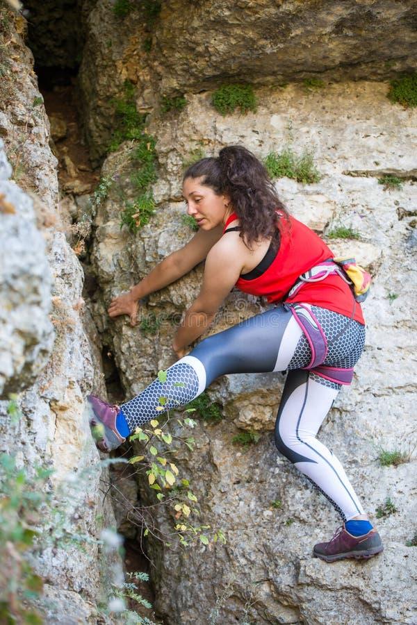 Foto van het jonge donkerbruine toerist beklimmen over rots stock foto's