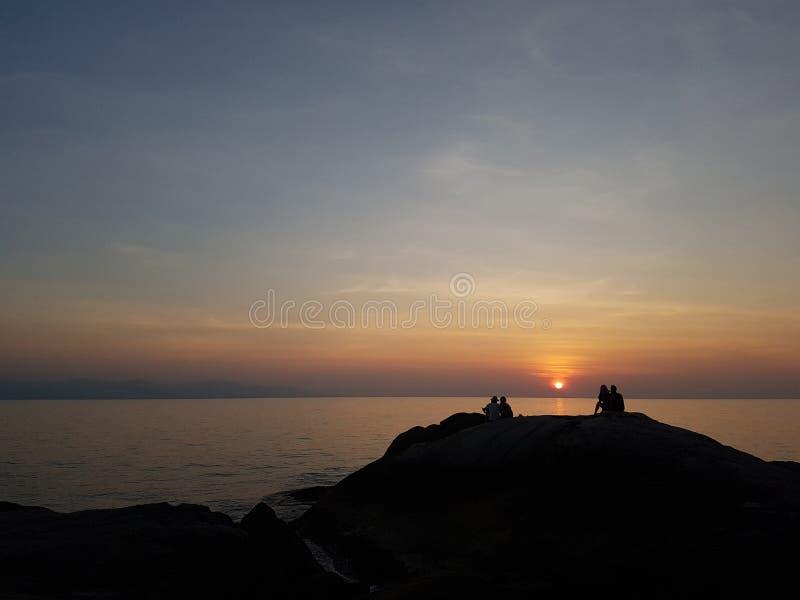 Foto van heuvel met gezette mensen bij zonsondergang op kust stock foto's