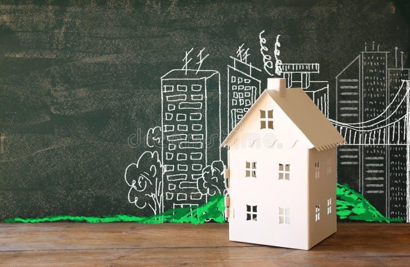 Foto van huis en achtergrond van bord en stadstekeningen onroerende goederen en het concept van het familiehuis royalty-vrije illustratie