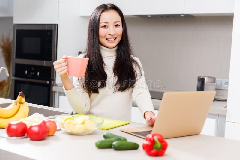 Foto van jong Aziatisch meisje met mok en laptop die zich bij lijst met groenten en vruchten bevinden stock foto