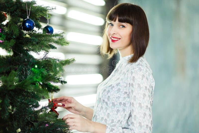 Foto van jong brunette dichtbij Nieuwjaar` s spar royalty-vrije stock foto