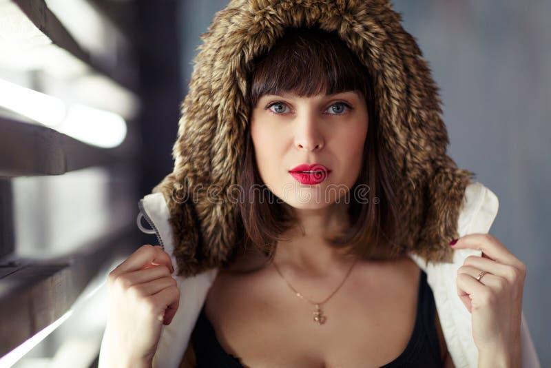 Foto van jong brunette in jasje met bontkap royalty-vrije stock afbeeldingen
