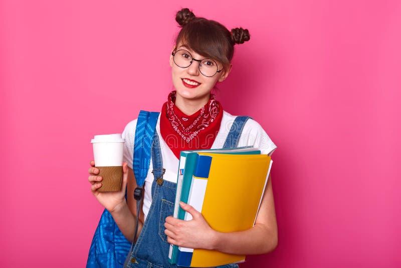 Foto van jong slank donkerbruin meisje die in witte toevallige t-shirt, overall en bandana op hals, kop van koffie en omslag houd royalty-vrije stock afbeelding