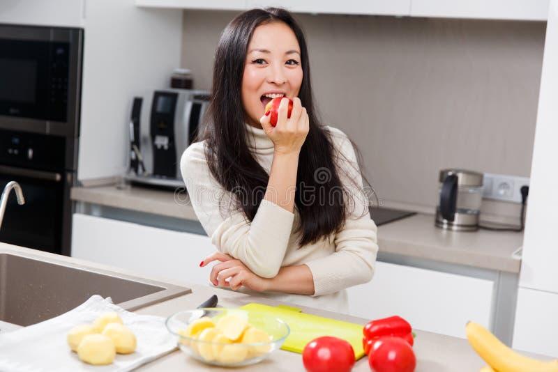 Foto van jonge donkerbruine het bijten appel terwijl status bij lijst met groenten en vruchten royalty-vrije stock foto's