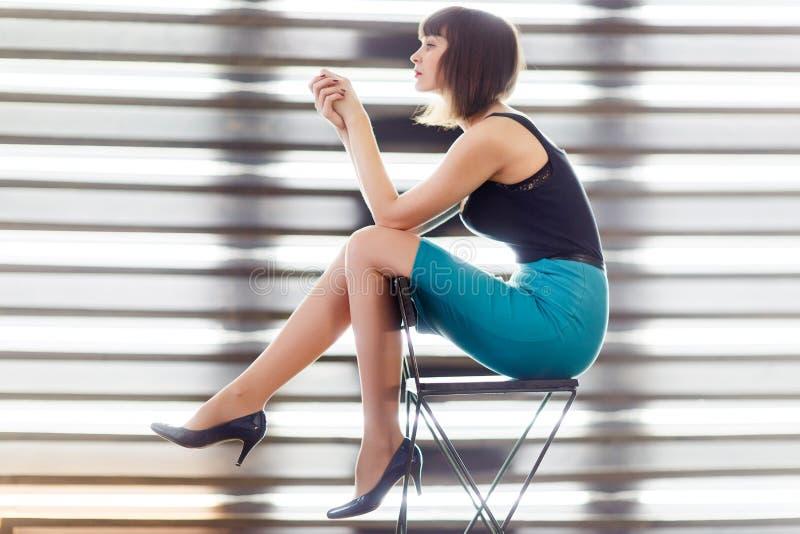 Foto van jonge donkerbruine zitting op stoel dichtbij venster met zonneblinden royalty-vrije stock afbeeldingen