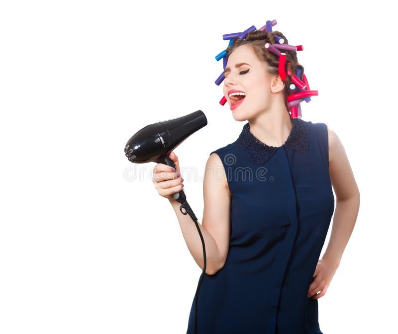 foto van jonge zingende vrouw in krulspeld met hairdryer royalty-vrije stock foto's