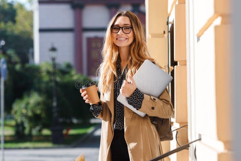 Foto van joyous laptop van de vrouwenholding terwijl het lopen door stadsstraat stock foto