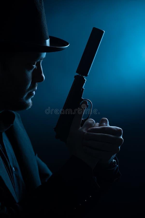 Foto van kant van de mens in zwarte hoed met pistool stock foto