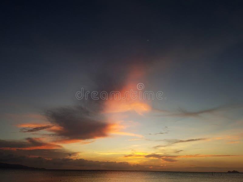 Foto van karmozijnrode hemel en overzeese kust met boot bij zonsondergang stock fotografie