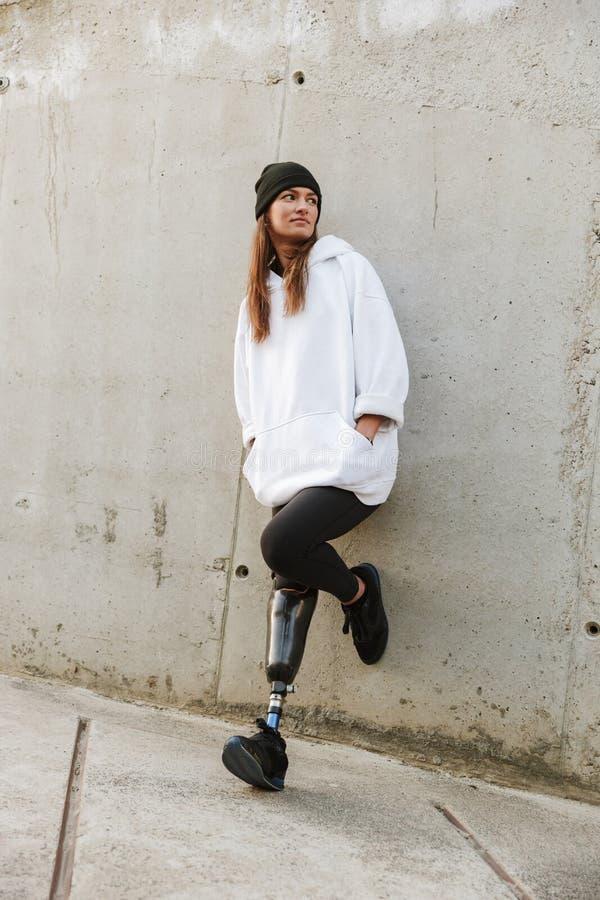 Foto van Kaukasisch gehandicapt meisje met bionisch been in vrijetijdskleding, stock fotografie