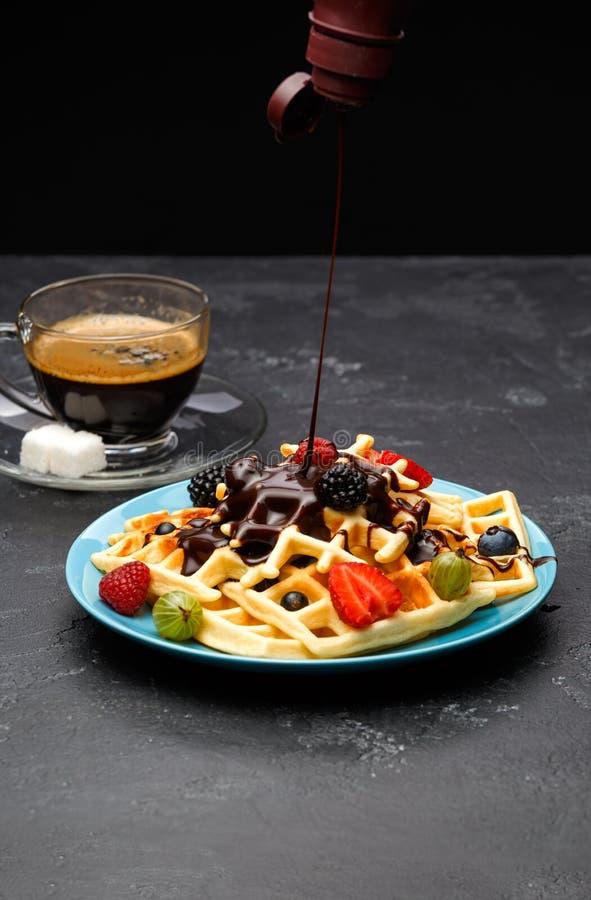 Foto van kop van zwarte koffie met suiker met Weense wafels met aardbeien, frambozen, kruisbessen en chocolade stock foto's