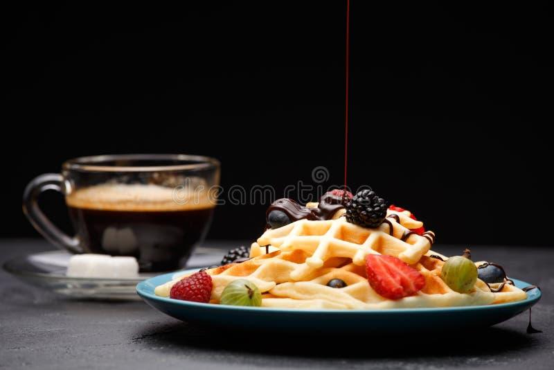 Foto van kop van zwarte koffie met suiker met Weense wafels met aardbeien, frambozen, kruisbessen en chocolade stock fotografie