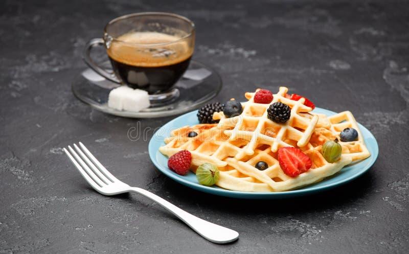 Foto van kop van zwarte koffie met suiker met Weense wafels met aardbeien, frambozen, kruisbessen en vork stock foto's