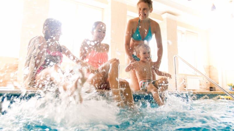 Foto van leuke peuterjongen met jonge moeder en oudere zusterzitting bij de pool en het bespattende water Familie het spelen en royalty-vrije stock foto's